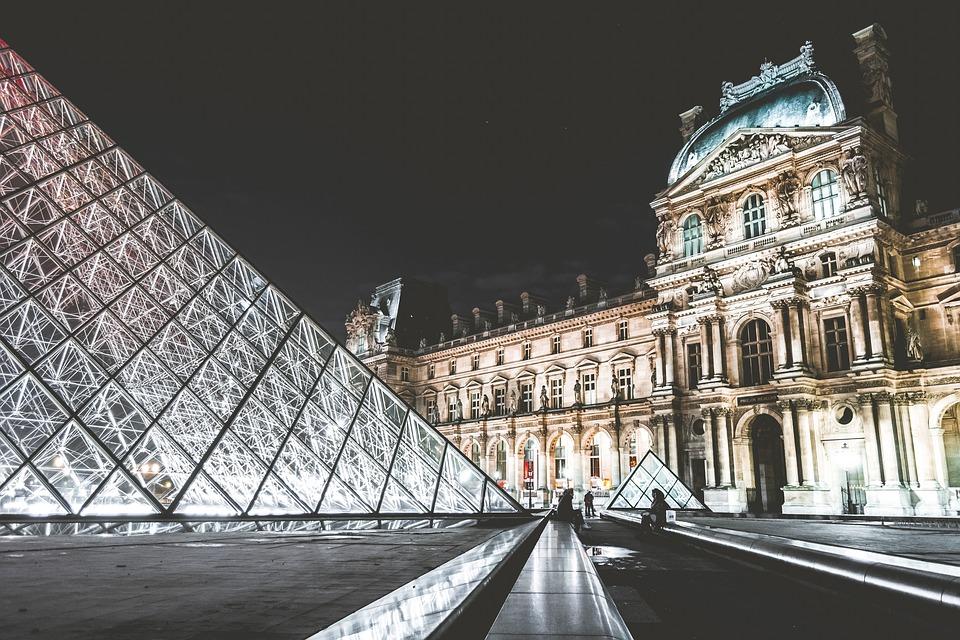 La pyramide du Louvre éclairée la nuit.